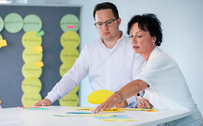 Bild zweier Mitarbeiter:innen, die sich um die Optimierung eines Online-Shops kümmern.